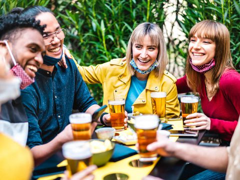 Multiracial people drinking beer with opened face mask - New normal friendship concept with friends having fun together on happy hour at brewery garden party - Vivid filter with focus on yellow jacket
