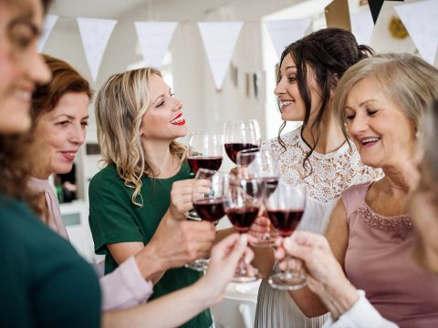 A multigeneration family clinking glasses with red wine on a indoor family birthday party, making a toast.